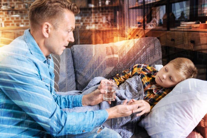 Baczny ojciec daje szkłu woda i pigułki jego dziecko fotografia stock