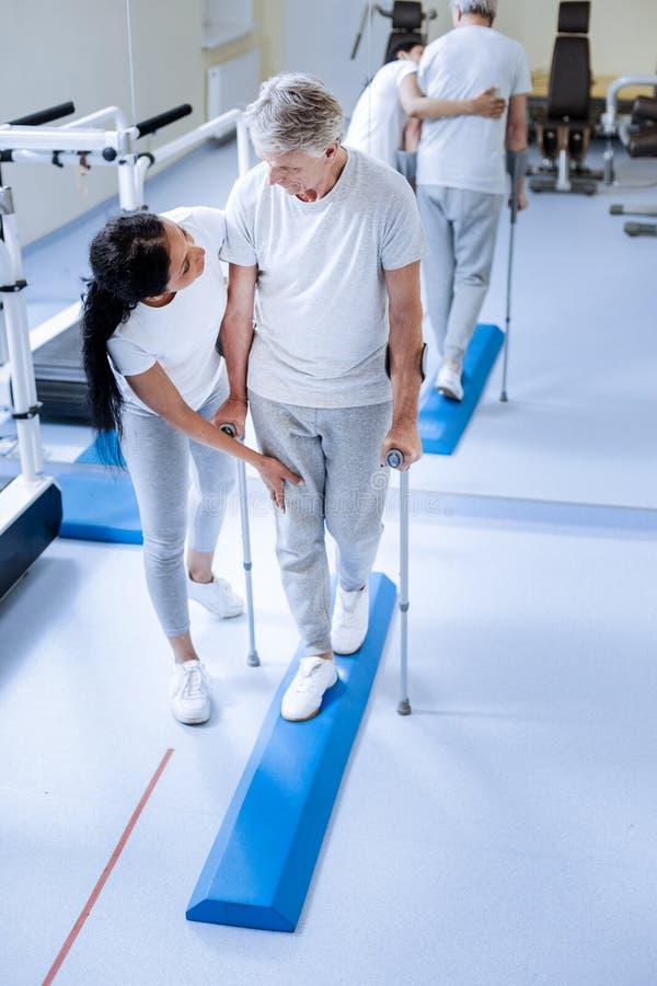 Baczny pomocniczo medyczny pracownik dotyka zdradzoną nogę jej starszy pacjent obraz royalty free