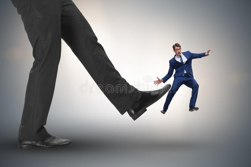 The bad angry boss kicking employee in business concept. Bad angry boss kicking employee in business concept royalty free stock image