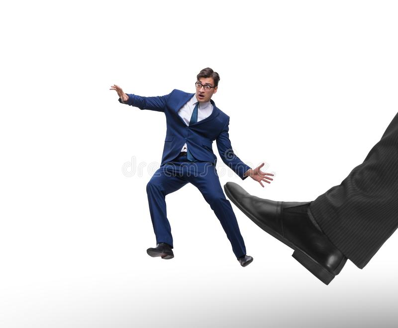 Bad angry boss kicking employee in business concept. The bad angry boss kicking employee in business concept royalty free stock photo
