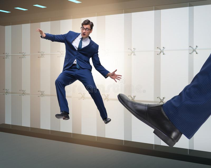 Bad angry boss kicking employee in business concept. The bad angry boss kicking employee in business concept stock images