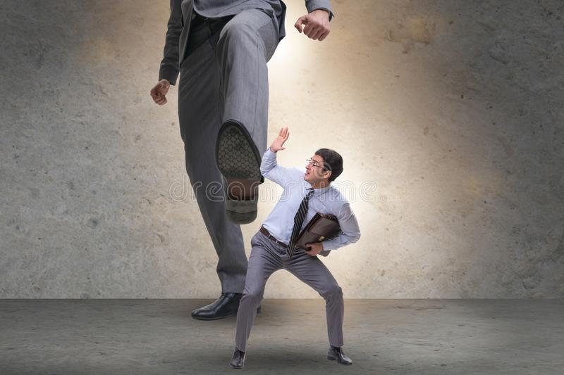 Bad angry boss kicking employee in business concept. The bad angry boss kicking employee in business concept stock photos