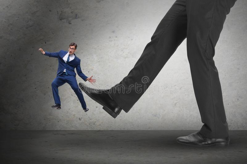 The bad angry boss kicking employee in business concept stock image