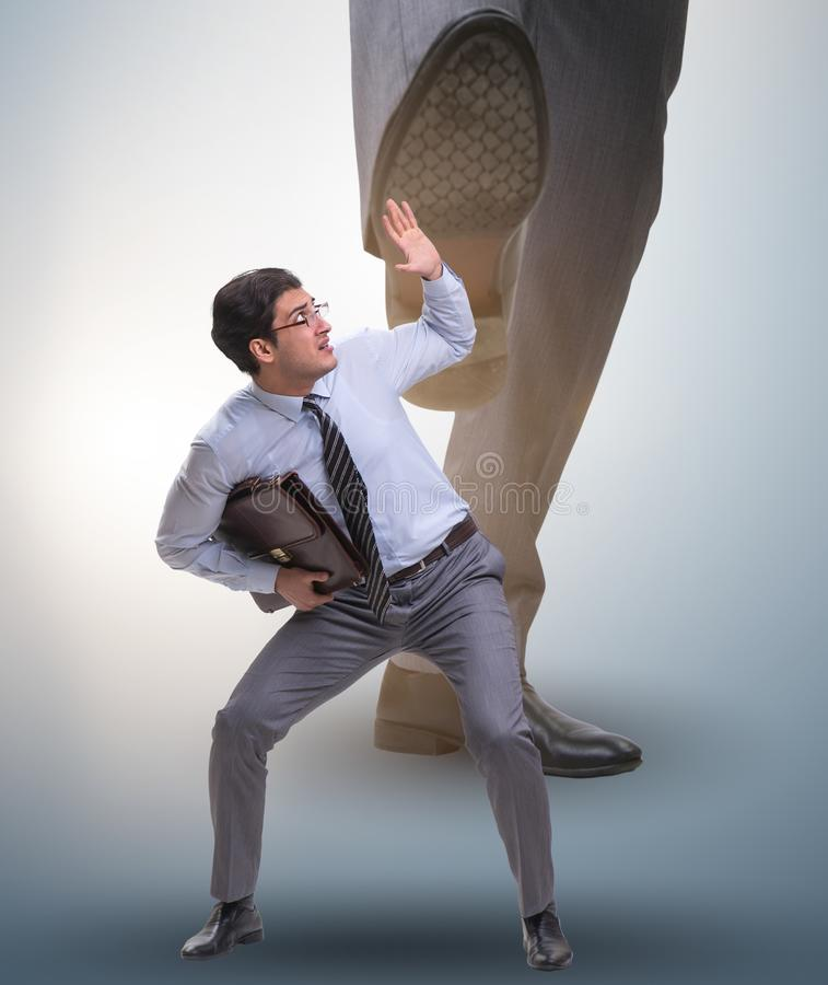 Bad angry boss kicking employee in business concept. The bad angry boss kicking employee in business concept stock photography