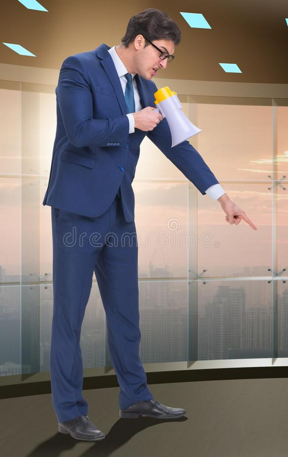 Bad angry boss shouting at employee with loudspeaker. The bad angry boss shouting at employee with loudspeaker stock images