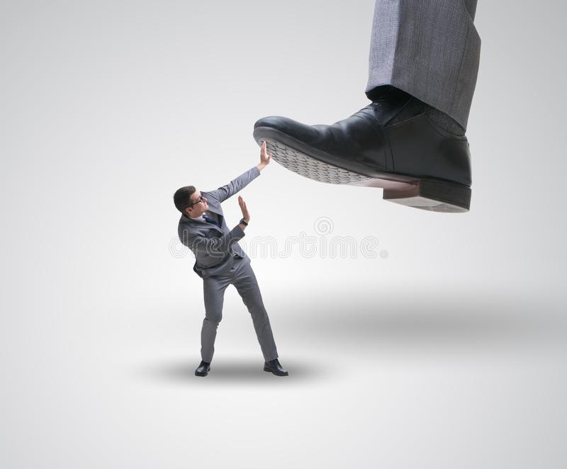 Bad angry boss stamping on employee in business concept. The bad angry boss stamping on employee in business concept royalty free stock image