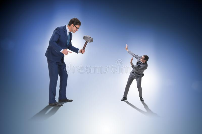 The bad angry boss threatening employee with hammer. Bad angry boss threatening employee with hammer stock photography