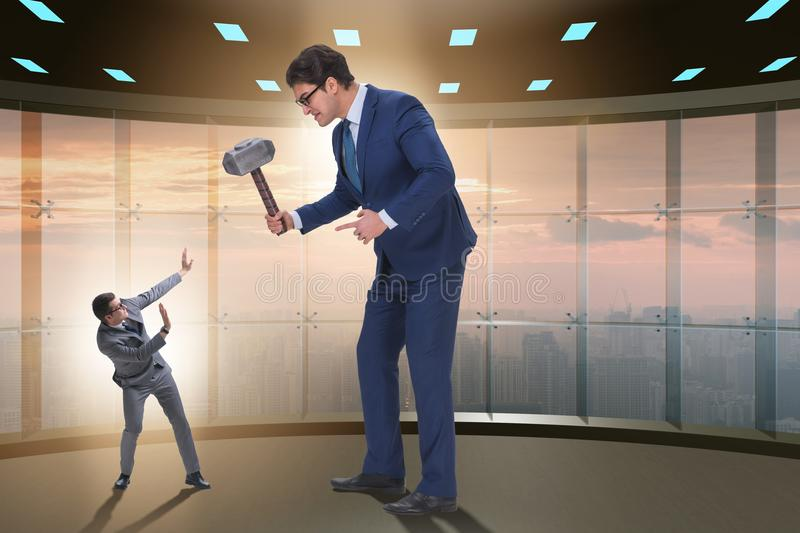 The bad angry boss threatening employee with hammer stock photo