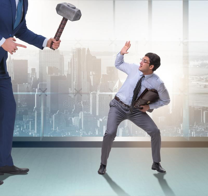 Bad angry boss threatening employee with hammer. The bad angry boss threatening employee with hammer royalty free stock photography