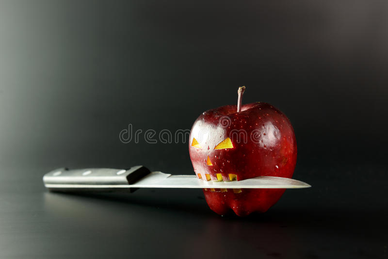 Bad apple. Apple with horror face and knife on it over black background stock image