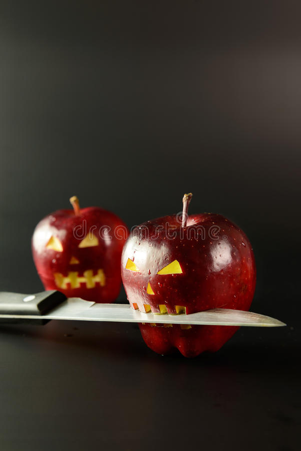 Bad apple. Apple with horror face and knife on it over black background stock photos