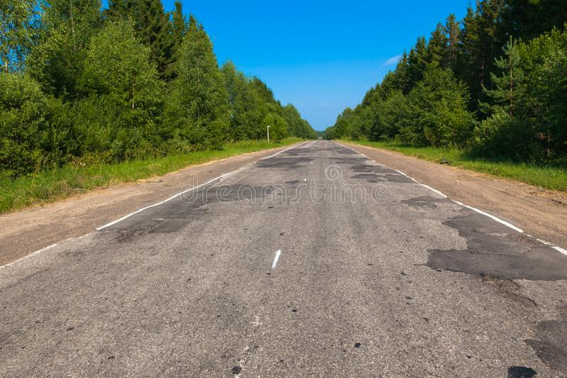Bad asphalt road in summer in Russia. Tver region. Russia. Bad asphalt road in summer in Russia. Tver region. Seliger. Russia royalty free stock photography