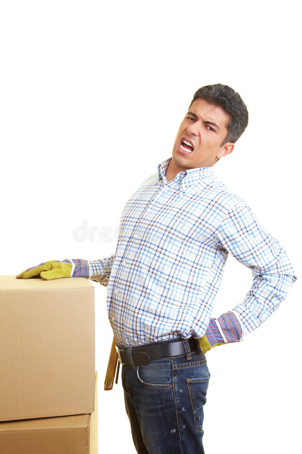 Bad back. Man with cardboard boxes has pain in his back royalty free stock photo