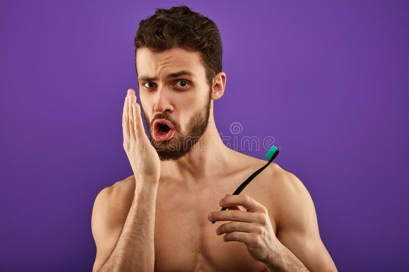 Bad breath. Young handsome man checking his breath with his hand. Blowing to it in the morning. bad smell from the mouth, toothache, guy having problems with stock photography