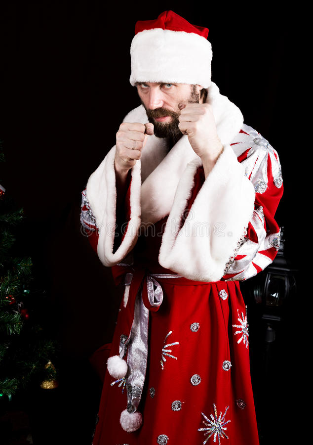 Bad brutal Santa Claus clenched his fists, ready to fight on the background of Christmas tree stock photography