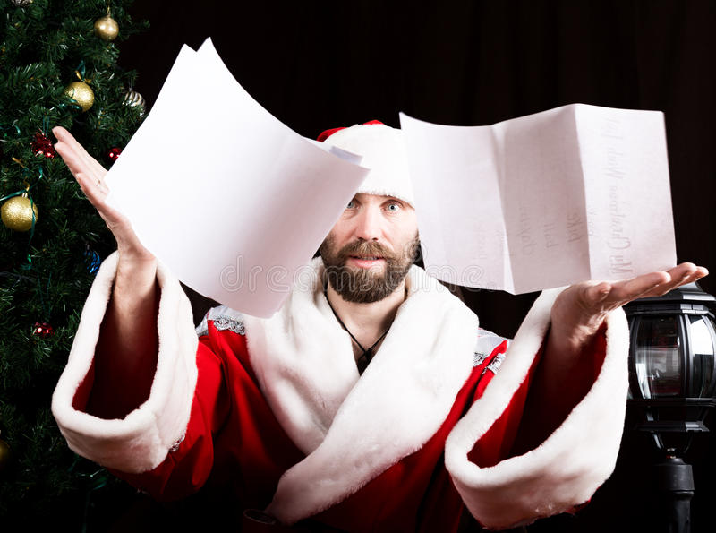 Bad brutal Santa Claus discontentedly reads letter with the wishes and throwing paper, on the background of Christmas stock photos