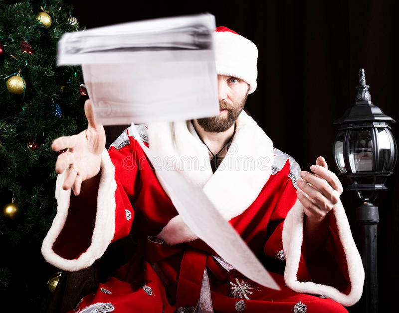 Bad brutal Santa Claus discontentedly reads letter with the wishes and throwing paper, on the background of Christmas royalty free stock photos