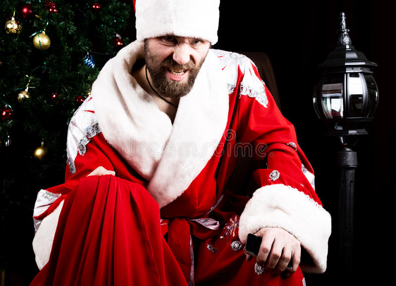 Bad brutal Santa Claus holding the bag with gifts on the background of Christmas tree stock photo