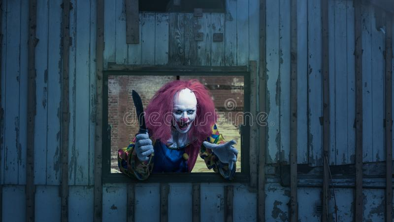 A bad clown with a knife looks out of a window royalty free stock images