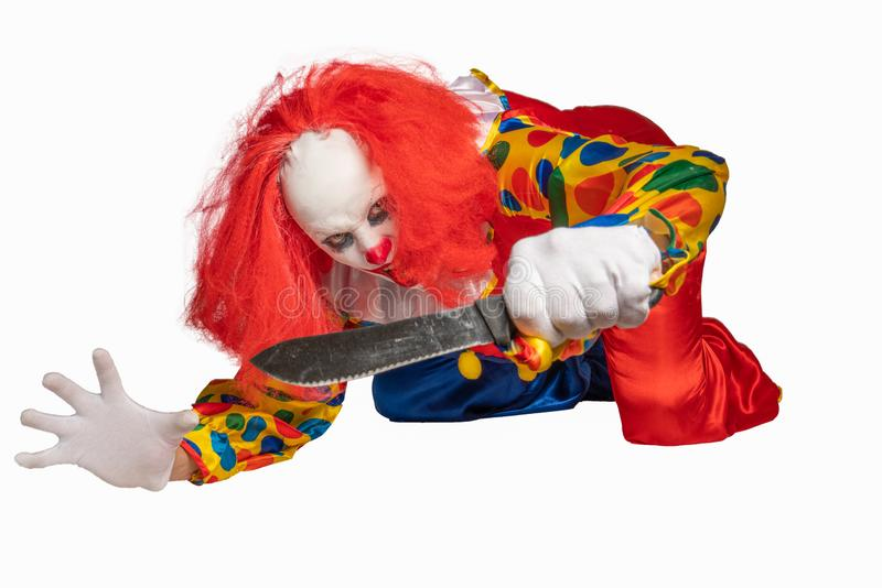 A bad clown lies on the ground and holds a knife in the camera royalty free stock images