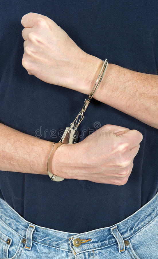 Bad Crook, Man Wearing Handcuffs, Law and Order. Concept for law, order, and justice. A man who is a crook or criminal is wearing handcuffs royalty free stock photo