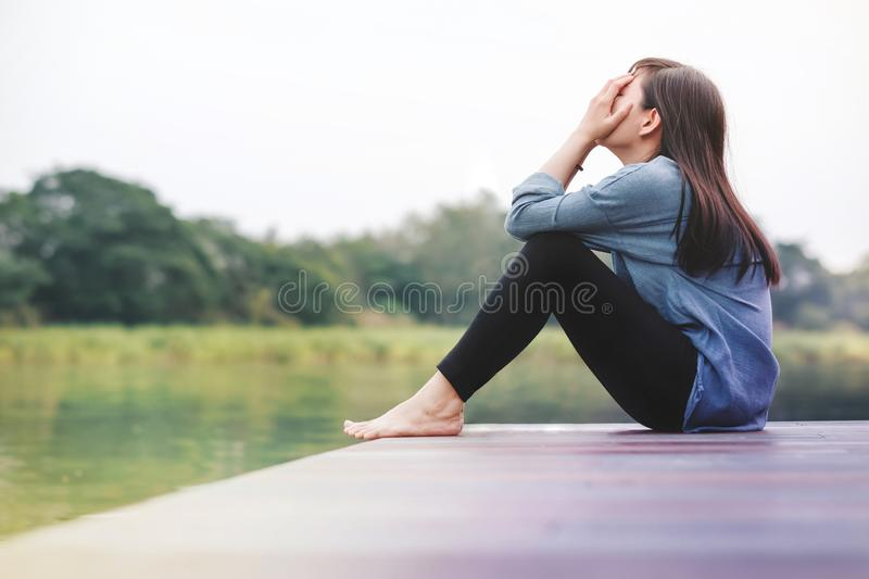 Bad Day Concept. Sadness Woman Sitting by the River. On Wooden Patio Deck. Faceless with Full Length Body, Side View stock photography