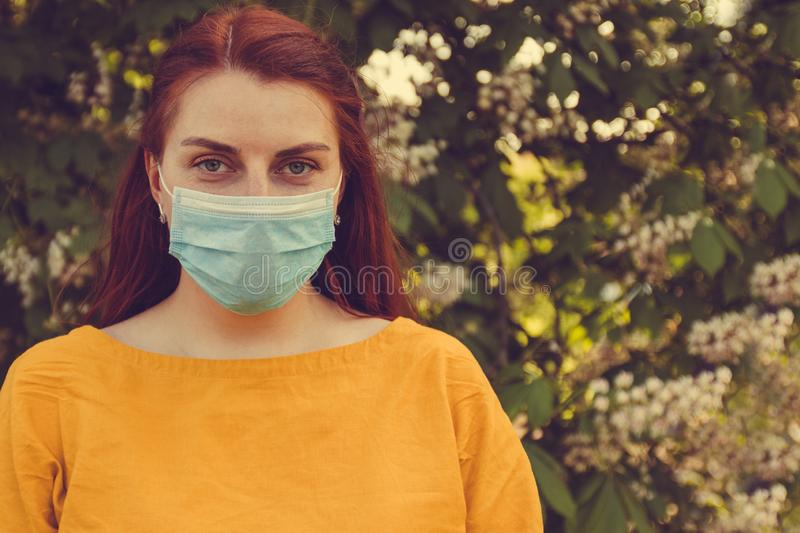Bad ecology and dirty air. A woman with red hair and a mask to protect against infections and viruses on the street. Medical concept. Allergy to flowering trees stock image