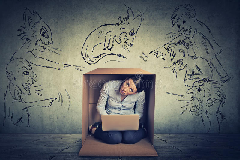 Bad evil men pointing at stressed woman sitting in a box. Bad evil man pointing at stressed woman. Desperate scared businesswoman hiding in a box working on royalty free stock photos