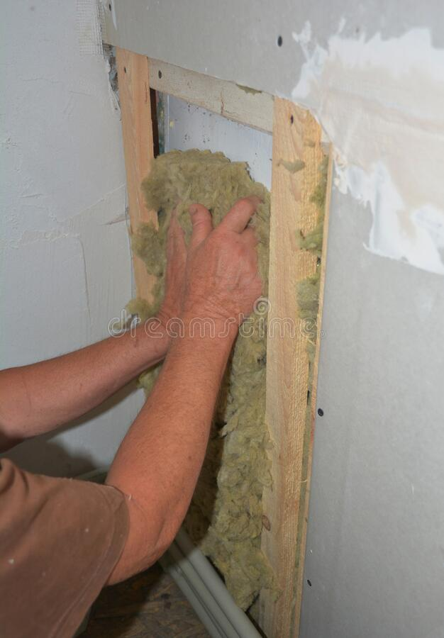 Bad example of indoor house fiberglass insulation without glowes. Worker hands insulating house drywall with rock wool stock photo