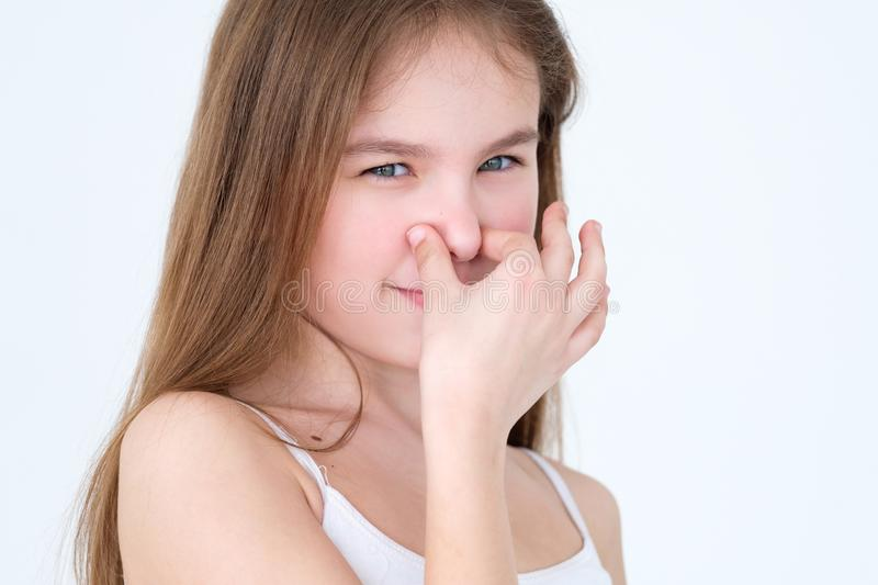 Bad foul smell stinky child cover nose expression. Bad foul smell. stinky odour. child covering her nose. little girl portrait on white background. facial stock images
