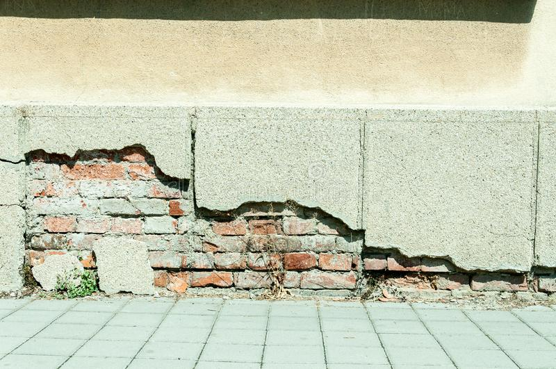 Bad foundation base on old house or building cracked plaster facade wall with brick background stock images