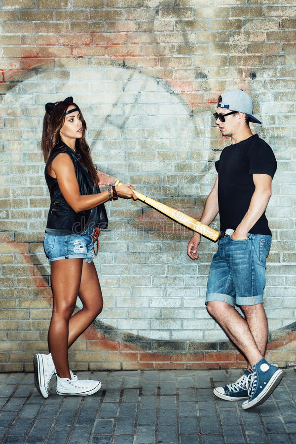Bad girl with leather cat ears threatening baseball bat guy. royalty free stock photography