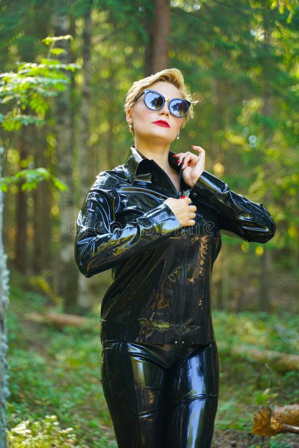 Latex rubber fashion woman walking in the forest. Bad girl wearing black shiny costume as protect and walking alone in the green hot summer forest stock photography