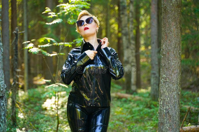 Latex rubber fashion woman walking in the forest. Bad girl wearing black shiny costume as protect and walking alone in the green hot summer forest stock photos