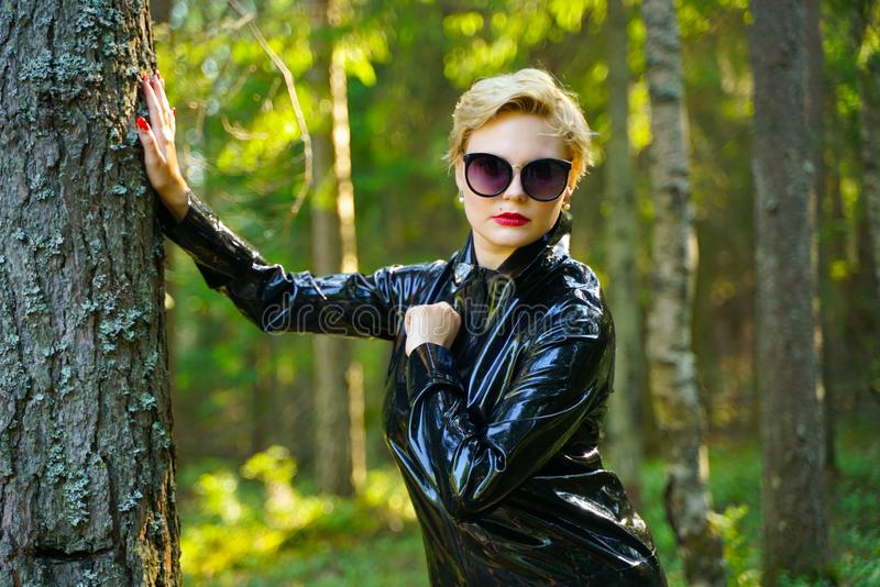 Latex rubber fashion woman walking in the forest. Bad girl wearing black shiny costume as protect and walking alone in the green hot summer forest royalty free stock images