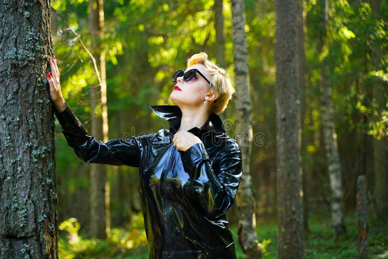 Latex rubber fashion woman walking in the forest. Bad girl wearing black shiny costume as protect and walking alone in the green hot summer forest stock image