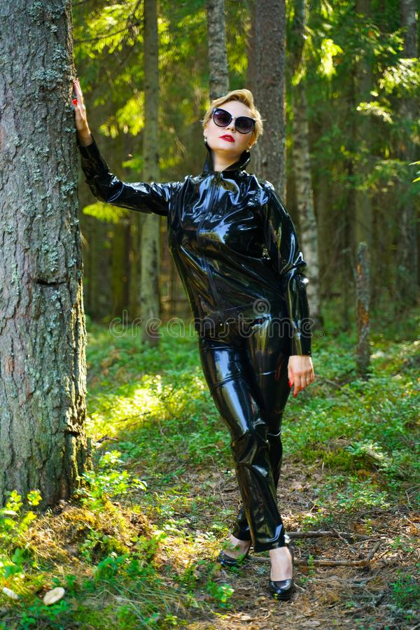 Latex rubber fashion woman walking in the forest. Bad girl wearing black shiny costume as protect and walking alone in the green hot summer forest royalty free stock image