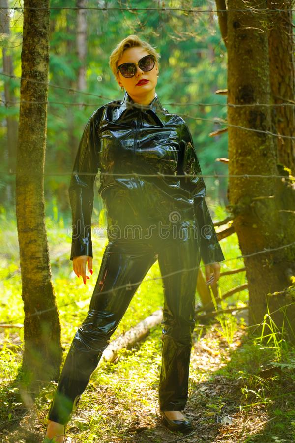 Latex rubber fashion woman walking in the forest. Bad girl wearing black shiny costume as protect and walking alone in the green hot summer forest royalty free stock photography
