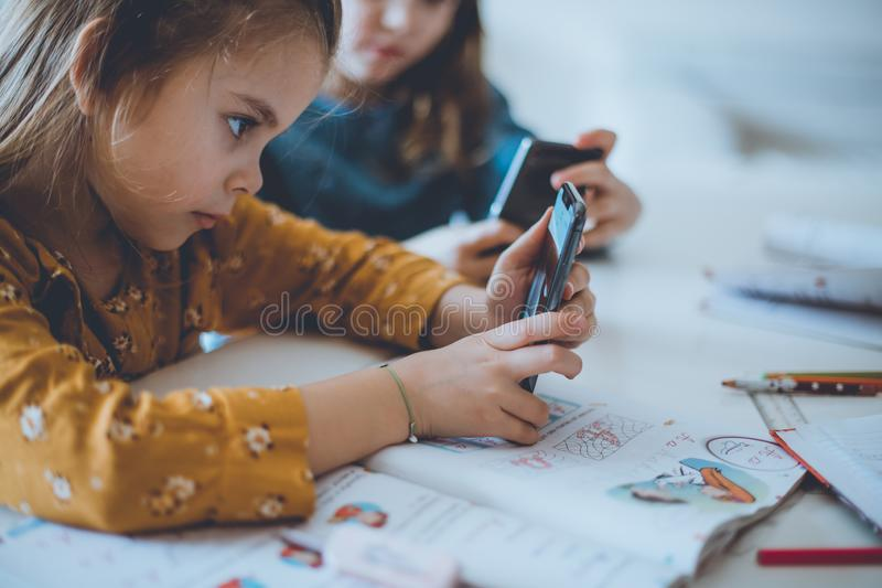 Bad habit. Two little girl using smart phone. Close up stock image