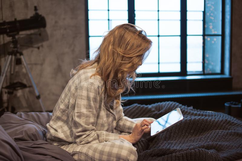Bad habits, girl takes to bed gadget, dependence on social networks stock photo