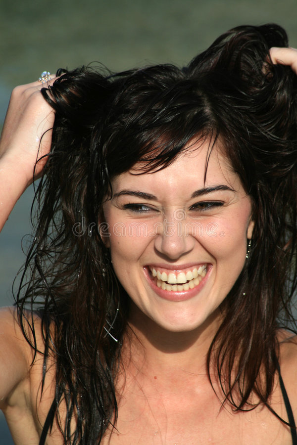 Bad hair day. A beautiful white caucasian woman with her hands in her wet brunette hair having a bad hair day and laughing stock photo