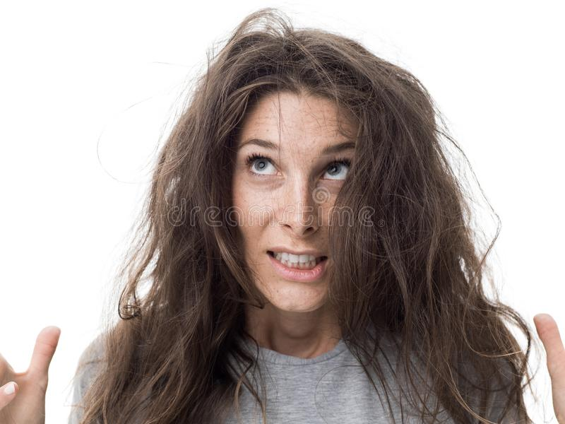 Bad hair day. Angry young woman having a bad hair day, her long hair is messy and tangled royalty free stock photography