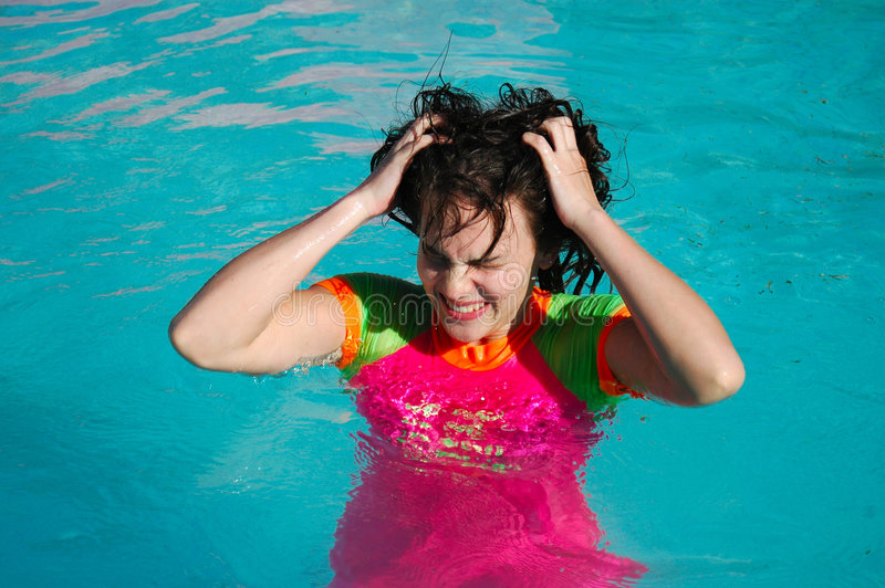Bad hair day in pool. Bad hair day for caucasian teen in swimming pool wearing colorful swimsuit stock image