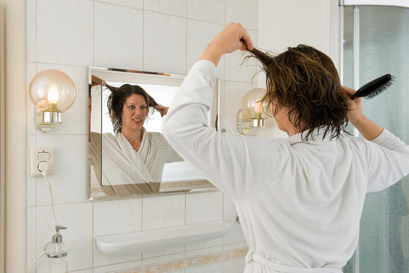 Bad hair day. A woman is looking in the mirror of the bathroom and having a 'bad hair day stock photos