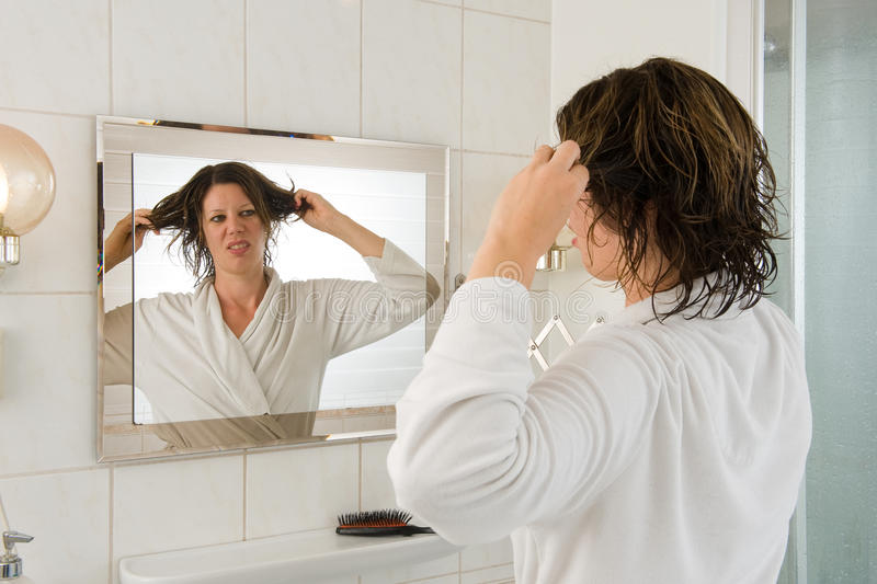 Bad hair day. A woman is looking in the mirror of the bathroom and having a 'bad hair day royalty free stock photo