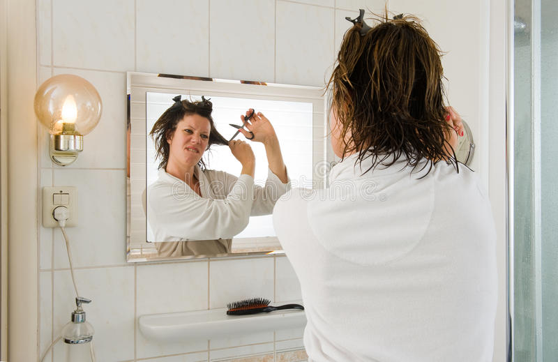 Bad hair day. A woman is looking in the mirror of the bathroom and having a 'bad hair day', and wants to cut her hair royalty free stock photography