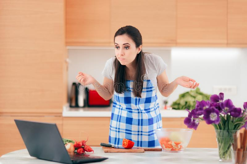 Cooking Woman Following Online Video Recipe on Laptop stock photography