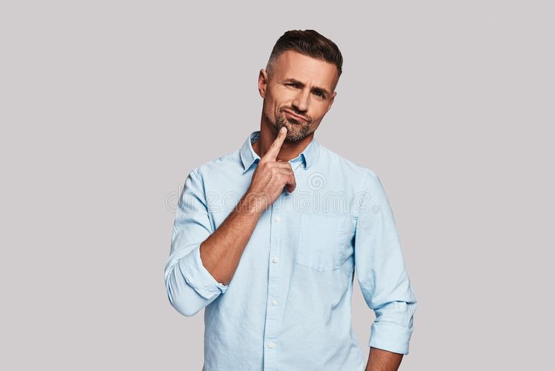 Bad idea. Thoughtful young man keeping hand on chin and making a face while standing against grey background stock image