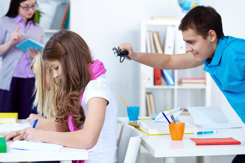 Bad joke. Evil lad holding black spider and going to frighten his classmates at lesson stock image