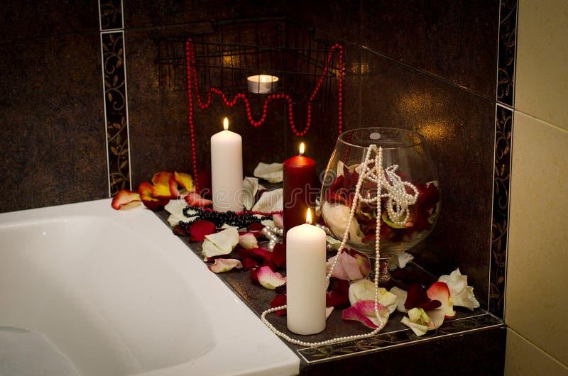 Bad mit rosafarbenen petelas und Kerzen stockbild